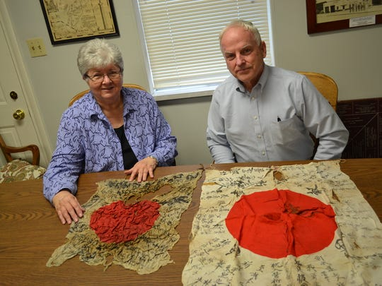 Peggy Debien and Jeff Brown sit at an Ottawa County Museum desk with the flags they hope to donate to the Obon Society, which will work with scholars and government agencies in an attempt to find the families of the flags' original owners. The writings on the flags often reveal the owners' names or home villages.
