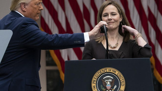 President Donald Trump adjusts the microphone after he announced Judge Amy Coney Barrett as his nominee to the Supreme Court, in the Rose Garden at the White House, Saturday, Sept. 26, in Washington.