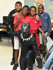 """Kenny Johnson is personal trainer and the owner of Top Notch Training, Inc.. But on Wednesday, he made a visit in costume as the Marvel Comics superhero """"Black Panther"""" to Club Esteem Youth & Family Center in Melbourne to surprise the after school program kids . He is helping to promote the opening of the highly acclaimed """"Black Panther"""" film and an opening night event at Cinema World 16 in West Melbourne on Friday, Feb. 16."""