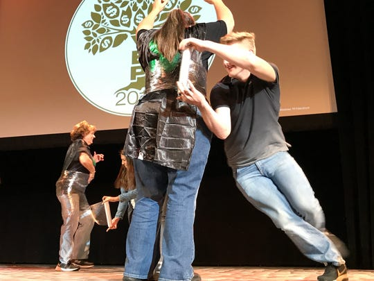 West Valley High student Dean Kerr, right, races to wrap plastic wrap around WV teacher Tiffanie Fife during a contest in between presentations at Thursday's competition finals of the Youth Entrepreneurship Program hosted by Shasta College at the Cascade Theatre.