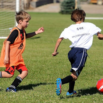 Luke Jerstad, 9, chases after Gavin Shields, 10 with the ball during a drill at the West Ham United soccer camp Wednesday morning at the Dakota Alliance training grounds in Harrisburg, July 28, 2015. July 28, 2015.