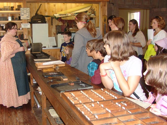 Interpreter Lasha Philabaum explains what printing was like in the 1800s to visitors in the Hay Craft & Learning Center.