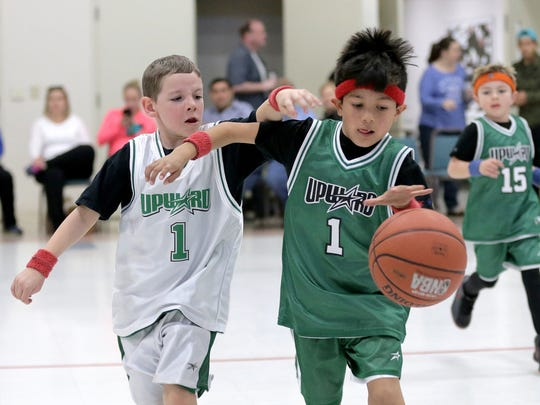 Cesar Jurado, right, dribbles the ball while being defended by Parker Taylor during their league game with the Upward Sports Program.