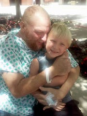 Jerry Faust hugs his grandson, Cameron James, in the courtyard at The Ohio State University Wexner Medical Center in Columbus. Faust was placed on the transplant list in June 2015 and received his new liver within a few days.