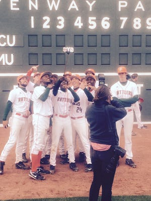 Florida A&M players pose a photograph in front of the Green Monster scoreboard in Fenway Park.
