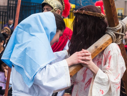 Jesus, played by Darvin Diaz, is met by Mary, played by Bernadette Santini, during the Good Friday procession down Almond Street on Friday in Vineland.