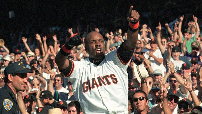 In this 1997 file photo, San Francisco Giants outfielder Barry Bonds celebrates on top of the Giants dugout after they beat the San Diego Padres to win the National League West title.