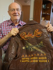 Howard Games holds up his hand-painted flight jacket from World War II. Games served as a B-26 pilot and flew 62 missions, including D-Day on June 6, 1944.