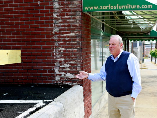 Scott Thompson, who with his wife, Sandra Graham, owns the Zarfos Furniture building, talks Wednesday, May 31, 2017, about Red Lion's new parking lot, which is adjacent to the couple's property in the borough. The couple recently won a lawsuit against the borough for essentially using their building as a retaining wall for the lot, with the court ruling the act trespassing. Dawn J. Sagert photo
