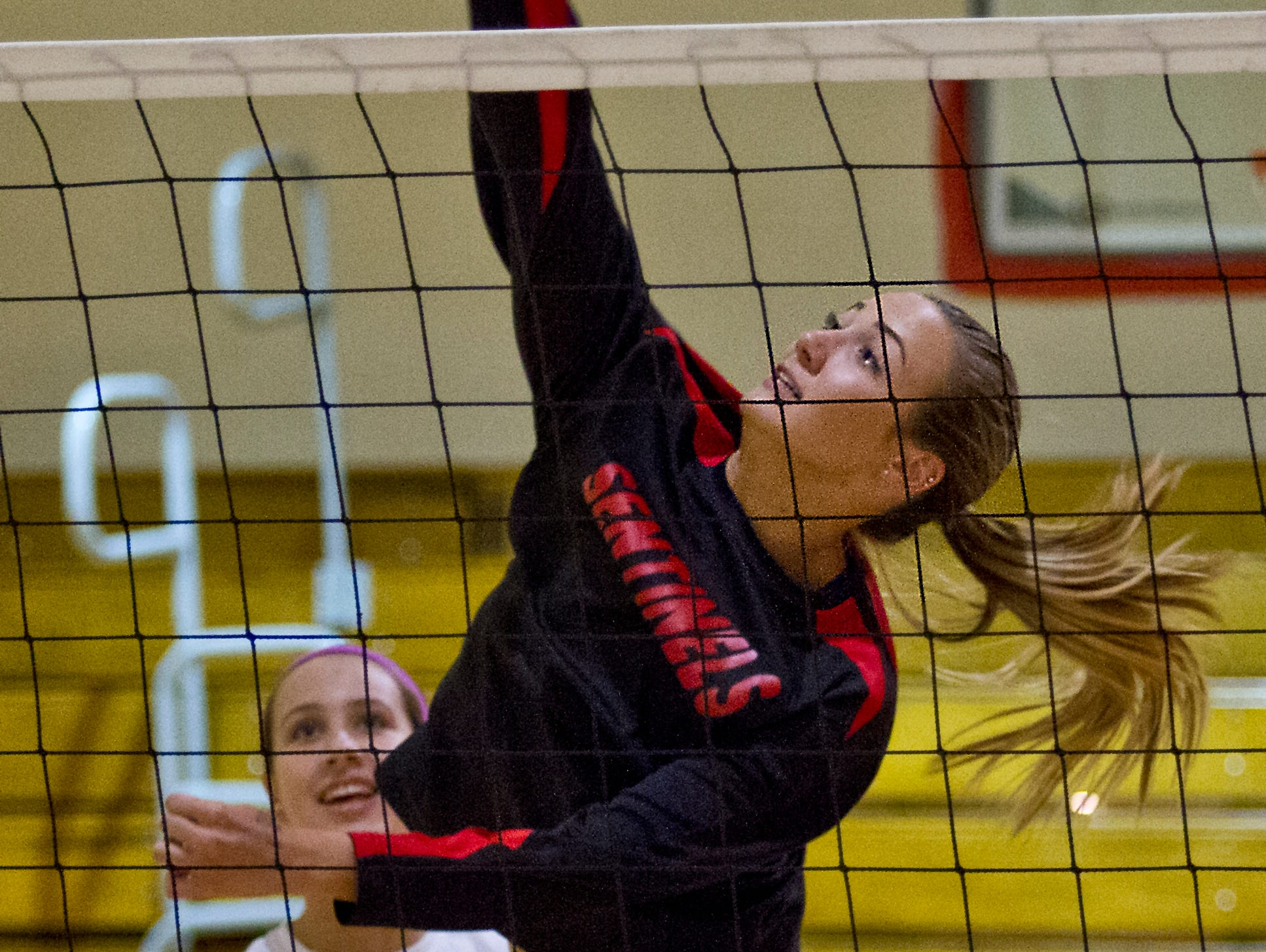 Emily Laquidara of ECS in Fort Myers goes high for a spike during team volleyball practice drills Monday (10/19/15).