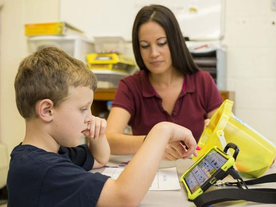 Liam Wilson works with teacher Valerie Carmack using a tablet as an alternative communication device at The Bancroft School in Haddonfield.