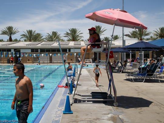 A lifeguard uses an umbrella for sun protection at the Palm Desert Aquatic Center June 6, 2017.