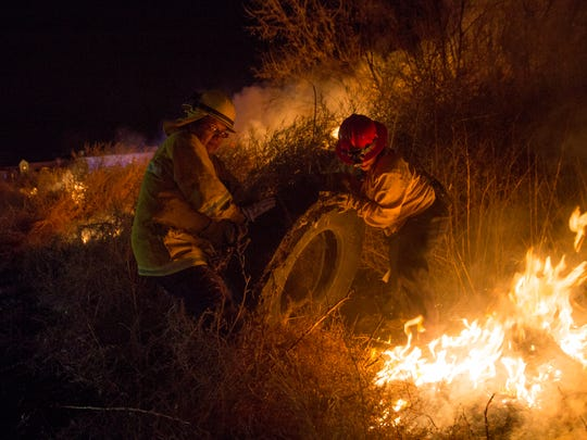 Members of the San Juan County Fire Department remove a large tire from a wildfire Saturday in Bloomfield.