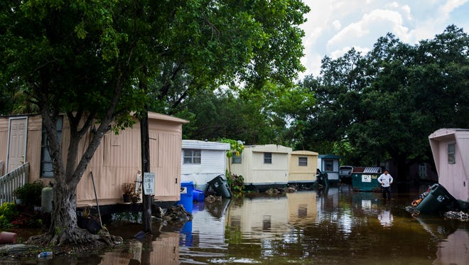 Antonio Ventura, 39, stands in the flooded street of a trailer park off Oakland Drive in Bonita Springs on Monday, Aug. 28, 2017.