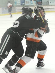Northville's Riley Brass (right) absorbs a  cross-check from Novi's Ryan Wexler during Tuesday's KLAA Central hockey clash at Novi Ice Arena.