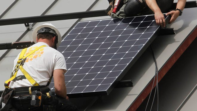 Workers install a solar panel in 2013 in Montpelier, Vt.