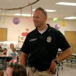 """Officer Chris Rutherford answers questions from Kindergarteners at John F. Kennedy Montessori Elementary, during Councilwoman Jessica Green's """"Prevention is better than Prosecution"""" event . Kindergarteners met with police officers and shared treats for """"Cupcakes with a Cop"""" where they could ask officers questions about their jobs. May 27, 2015"""