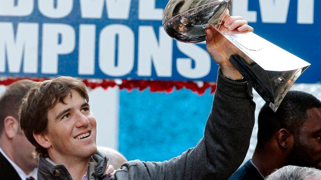 From Feb. 7, 2012, New York Giants quarterback Eli Manning holds up the Vince Lombardi Trophy during the team's NFL football Super Bowl parade in New York. Manning, who led the Giants to two Super Bowls in a 16-year career that saw him set almost every team passing record, has retired. The Giants said Wednesday, Jan. 22, 2020 that Manning would formally announce his retirement on Friday.