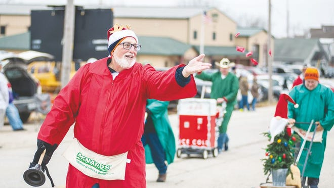 A Christmas themed parade walker throws candy to children attending the 2019 Lake Ozark Christmas Parade.