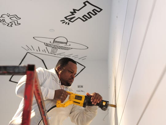 Rodney Hairston with Turnbull-Wahlert Construction tears out a wall at the Center for Contemporary Art on Tuesday. The CAC is renovating its lobby to be more welcoming.