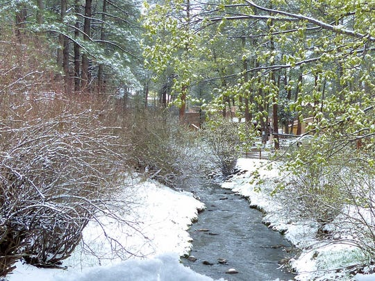 The late spring snow delivered some moisture to a forest that was drying out quickly, and should help put out any remaining hidden embers from fires that ignited Monday.