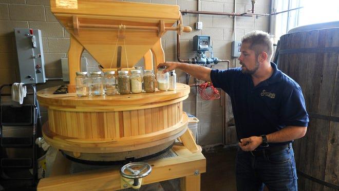 Head distiller Greg Eidam shows a mill at Sugarlands Distilling Co. in Gatlinburg on April 16, 2015.