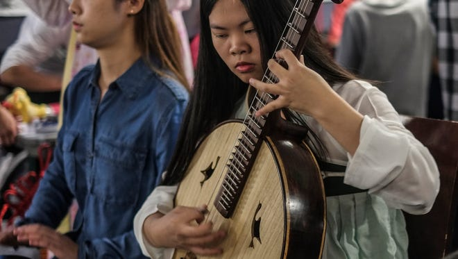 A Chinese student plays a stringed instrument along with other students at the Global Festival at the MSU Union Sunday, November 13, 2016.