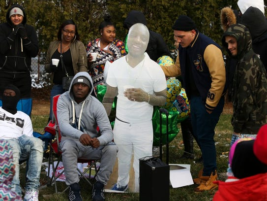 Friends and Family gather around a cutout image of