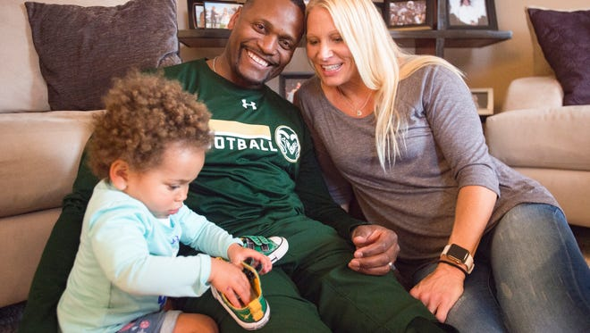 CSU receivers coach Alvis Whitted poses for a photo Monday with his wife, Tracy, and their 20th-month old daughter, Remy, at their Fort Collins home.