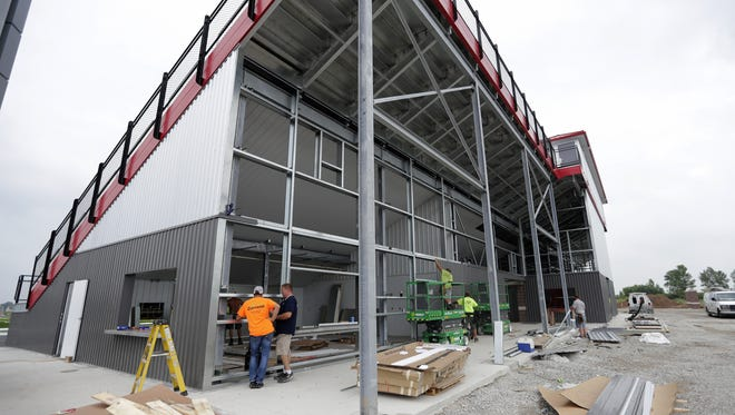 Workers are busy around the rear of the new Saputo Stadium at Pulaski High School. The ability of districts like Pulaski to raise funds for major capital projects is raising concerns that less affluent districts face increasing funding gaps.