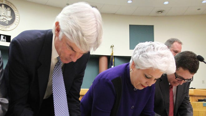 Rachel Denny Clow/Caller-Times Corpus Christi City Council members Mark Scott (from left), Mayor Nelda Martinez and Rudy Garza sign their oaths after being sworn onto the council before the start of the first council meeting in 2012.