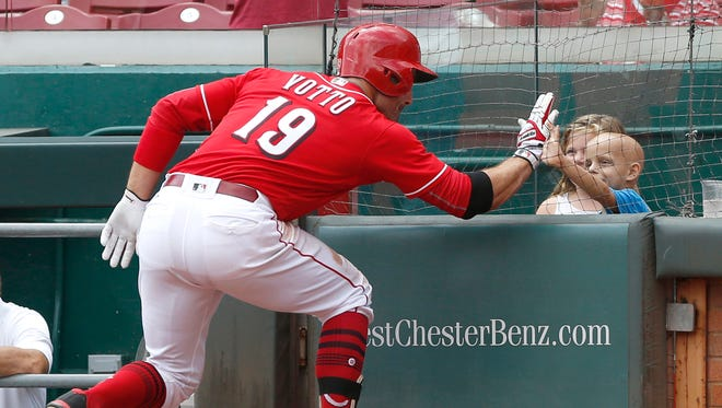 Cincinnati Reds first baseman Joey Votto (19) high fives six-year old Walter Herbert (right) after hitting a solo home run against the New York Mets in the seventh inning. Herbert is battling from stage 4 neuroblastoma.