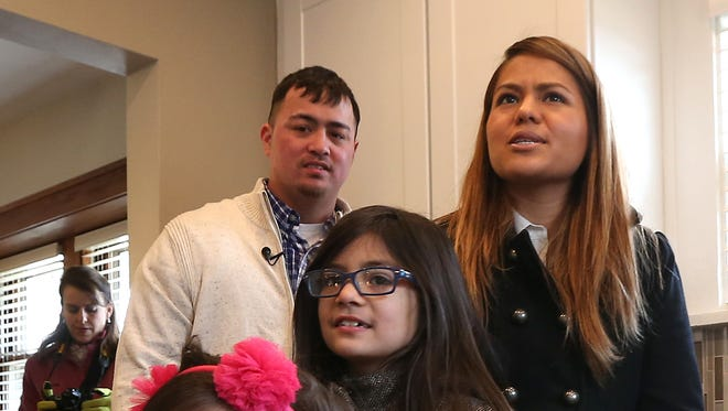 From left, Purple Heart recipient Bradly Hanawalt, Lively, 4, Honey Dawn, 8, and his wife, Carla, check out the kitchen of their new, mortgage-free home Thursday in Des Moines.