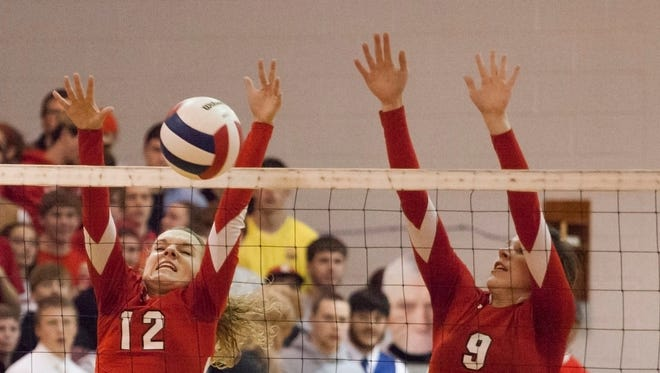 Riverheads' Mekayla Heizer, center, and teammate Jennifer Callison, right, jump to block a shot from Floyd County during their Group 2A state semi-final volleyball match on Tuesday, Nov. 18, 2014.