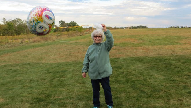 Marilyn Schaller holds one of her 90th birthday balloons.