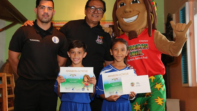 Gavin Baker, Kalle Damian and coach Ashley Besagar recently were recognized for their excellence and commitment to the United Airlines Guam Football Association National Academy at a ceremony at Jamaican Grill's Dededo location. Front, from left: Baker and Damian. Back, from left: Academy Director Dominic Gadia, Jamaican Grill restaurant manager Ray Barnes, and the Jamaican Grill Jerk Man. Not shown is Besagar.