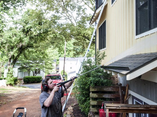 Shawn Johnson pressure washes a house in West Asheville last week. Johnson has become almost an urban legend among the 15,000 members of the West Asheville Exchange Facebook group. Down on his luck, Johnson found a supportive community and offers for handyman work as Shawn of All Trades.