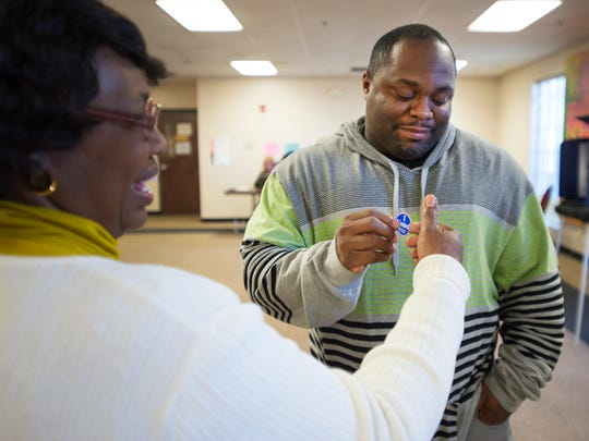 Elisha Shaw of Greenville is handed a sticker by poll manager Rosa Byrd after voting in the democratic primary at the West End Community Development Center on Saturday, February 27, 2016.