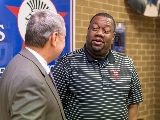 Broussard Middle Principal John Mouton, right, speaks to Superintendent Donald Aguillard after being named a Lafayette Parish principal of the year.
