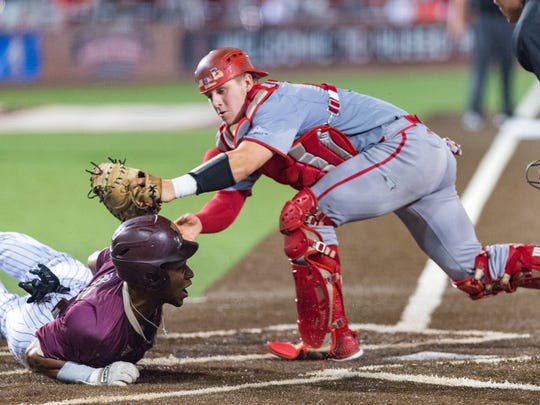 UL catcher Kole McKinnon tries to tag a Texas State runner in a game last May.