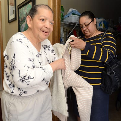 Denise Brown helps her cousin, Irene Collins, into