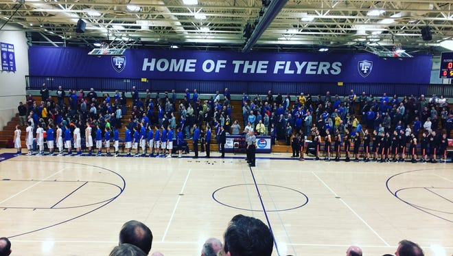 Players from Kimball High School (left) and Browerville/Eagle Valley stand for the national anthem Tuesday before playing in the South Sub-Section 5A boys basketball championship game in Little Falls. The Tigers beat the Cubs 61-55 to advance to the section championship game.
