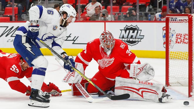 Red Wings goaltender Petr Mrazek (34) stops a Lightning right wing Nikita Kucherov (86) shot as Jonathan Ericsson (52) defends in the first period on Sunday, Jan. 7, 2018, at Little Caesars Arena.