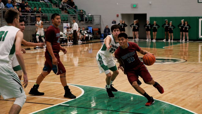 Farmington defender Chandler Corley, No. 23, looks to keep Shiprock ballhandler Kieon Harvey from attacking the basket during a game on Jan. 4 at Scorpion Arena.
