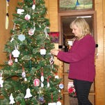 """Cheryl Osborn arranges ornaments on the Christmas tree at Showpiece Creations, 416 Main St. in Coshocton. Osborn encourages residents to shop local. """"Small businesses have a lot more to offer,"""" she said, adding that shopping small equals jobs."""