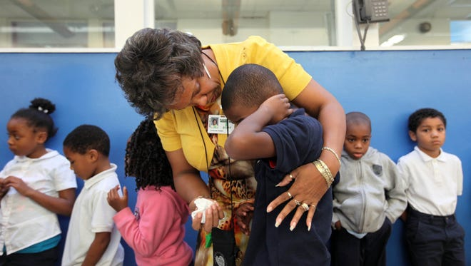 First grade teacher Charlene Rainer consoles a student who was upset in the lunchroom of Stubbs Elementary School, Wednesday, October 8, 2014.