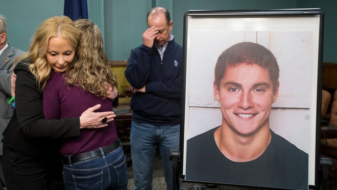 Centre County District Attorney Stacy Parks Miller, left, hugs Evelyn Piazza as her husband Jim stands in the background after announcing the findings in the investigation of the February death of the couple's son, Timothy Piazza, seen in photo at right, at Penn State University's fraternity Beta Theta Pi, Friday, May 5, 2017, in Bellefonte, Pa.  Piazza had toxic levels of alcohol in his body and was badly injured in a series of falls, authorities said Friday in announcing criminal charges against members of the organization and the frat itself.