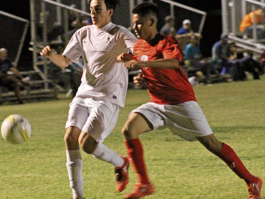 Tom Burnie-Burgeim, left, challenges a Las Cruces High player for possession Tuesday night at the Riner Steinoff Soccerplex.