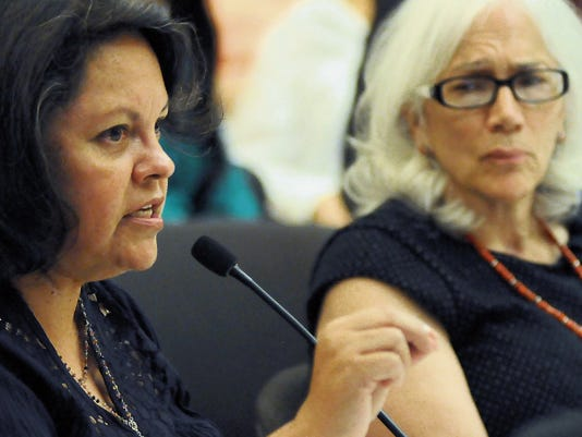 Suzan Martinez de Gonzales, director of La Clinica de Familia, a low-income primary care provider, left, speaks on Monday during a Mental Health Oversight Committee of Doña Ana County meeting in the Commission Chambers of the Doña Ana County Government Center to discuss the transition between La Frontera — the major Medicaid-funded behavioral health provider locally — and new providers. Looking on in the background is Dr. Denise Leonardi, UnitedHealthcare Community Plan of New Mexico chief medical officer.