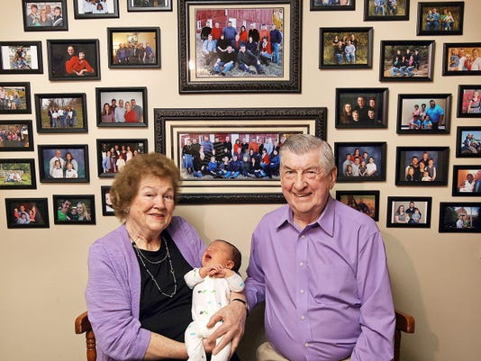 In this April 17, 2015 photo, Leo and Ruth Zanger sit with their 100th grandchild, Jaxton Zanger, in Leo's real estate office in Quincy, Ill.